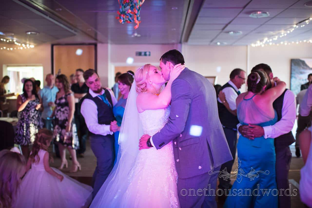 Bride and groom and guests kiss on dance floor at RLNI College Wedding