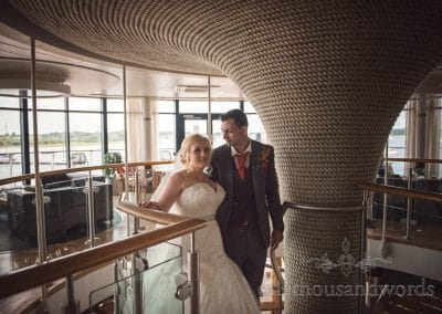 Bride and groom ascend rope clad staircase at RNLI College Wedding Photographs