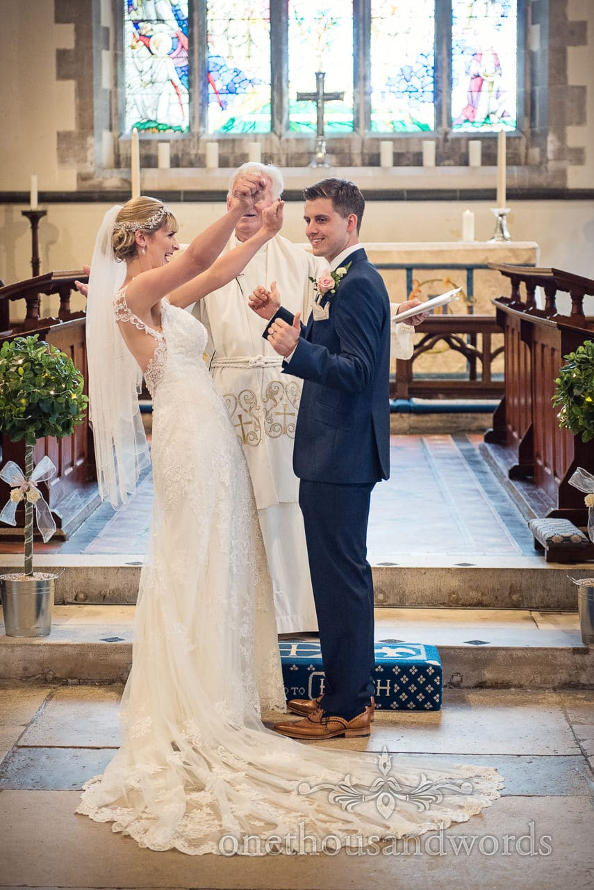 Bride and groom celebrate their marriage stood at church altar during ceremony