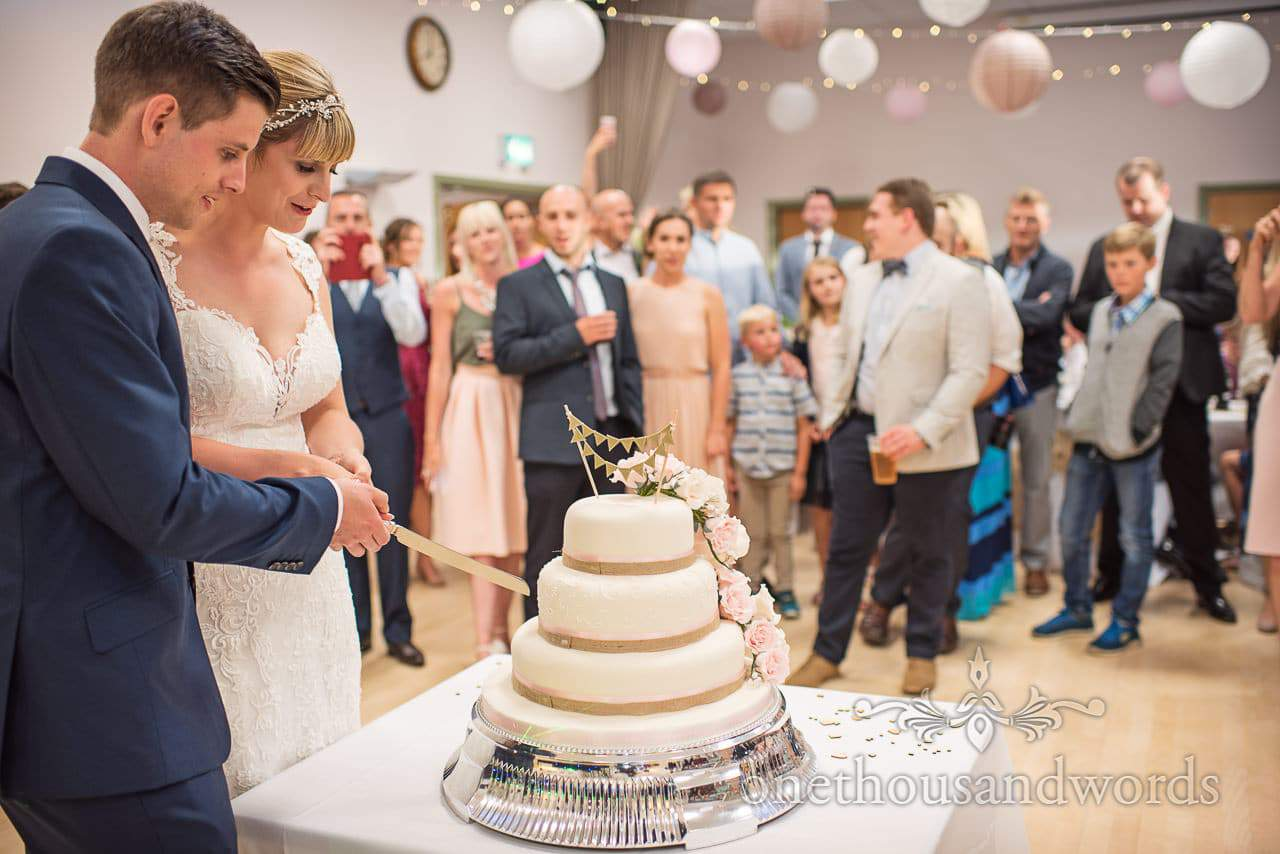 Bride and groom cut the cake at Harmans Cross Village Hall Wedding Photographs