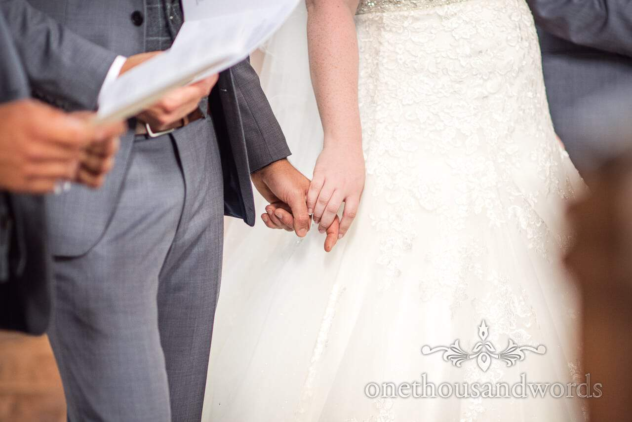 Bride and groom hold hands at Church wedding ceremony in Poole, Dorset