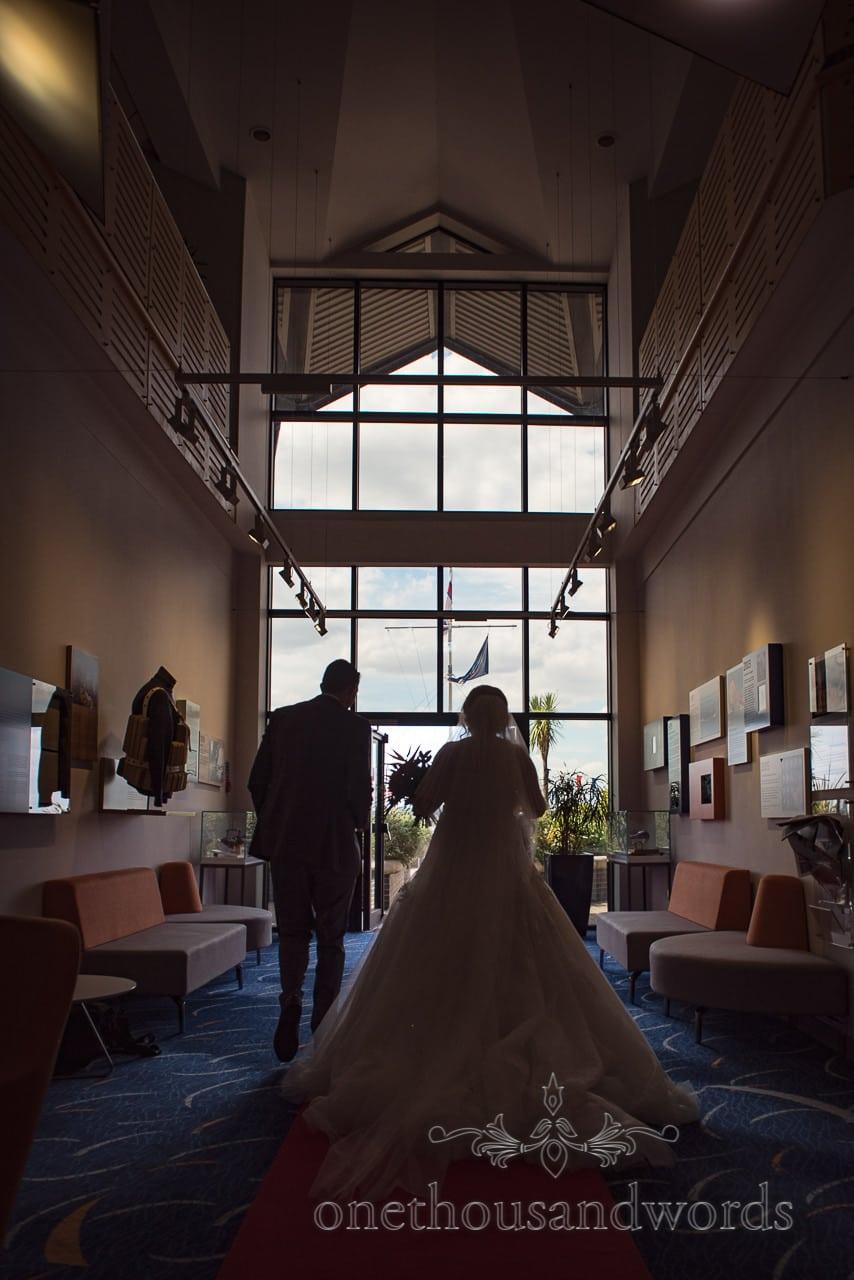 Bride and groom in silhouette walk through RNLI College Wedding venue in Poole