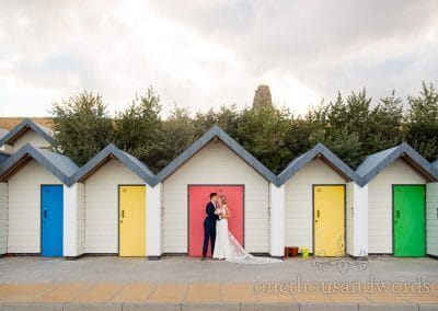 Bride and groom kiss in front of multicoloured beach hut doors in Swanage, Dorset