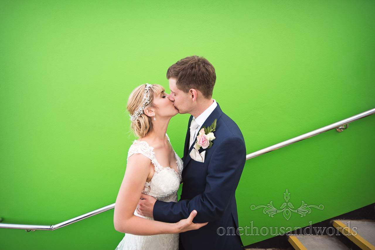 Bride and Groom kiss next to green wall backdrop on wedding in Swanage, Dorset
