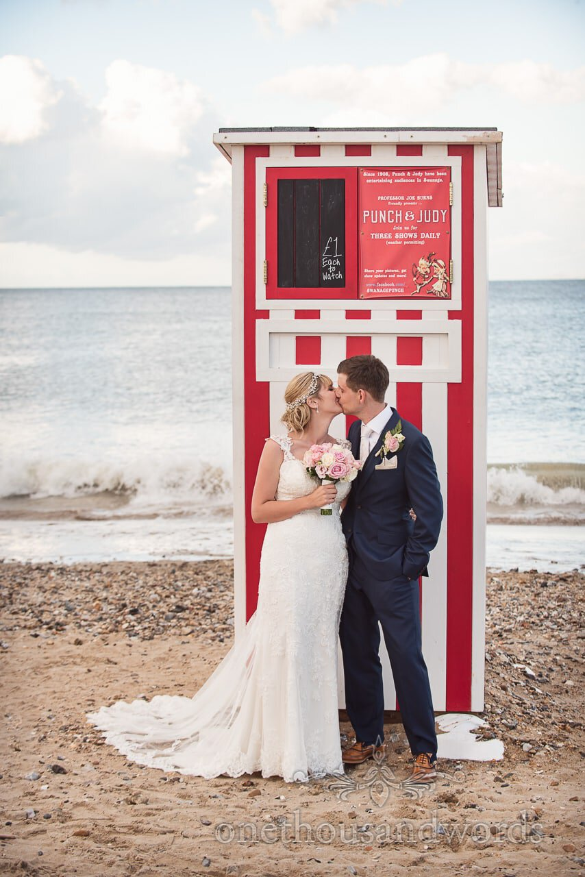 Bride and groom kiss on beach by sea in front of punch and Judy show in Dorset
