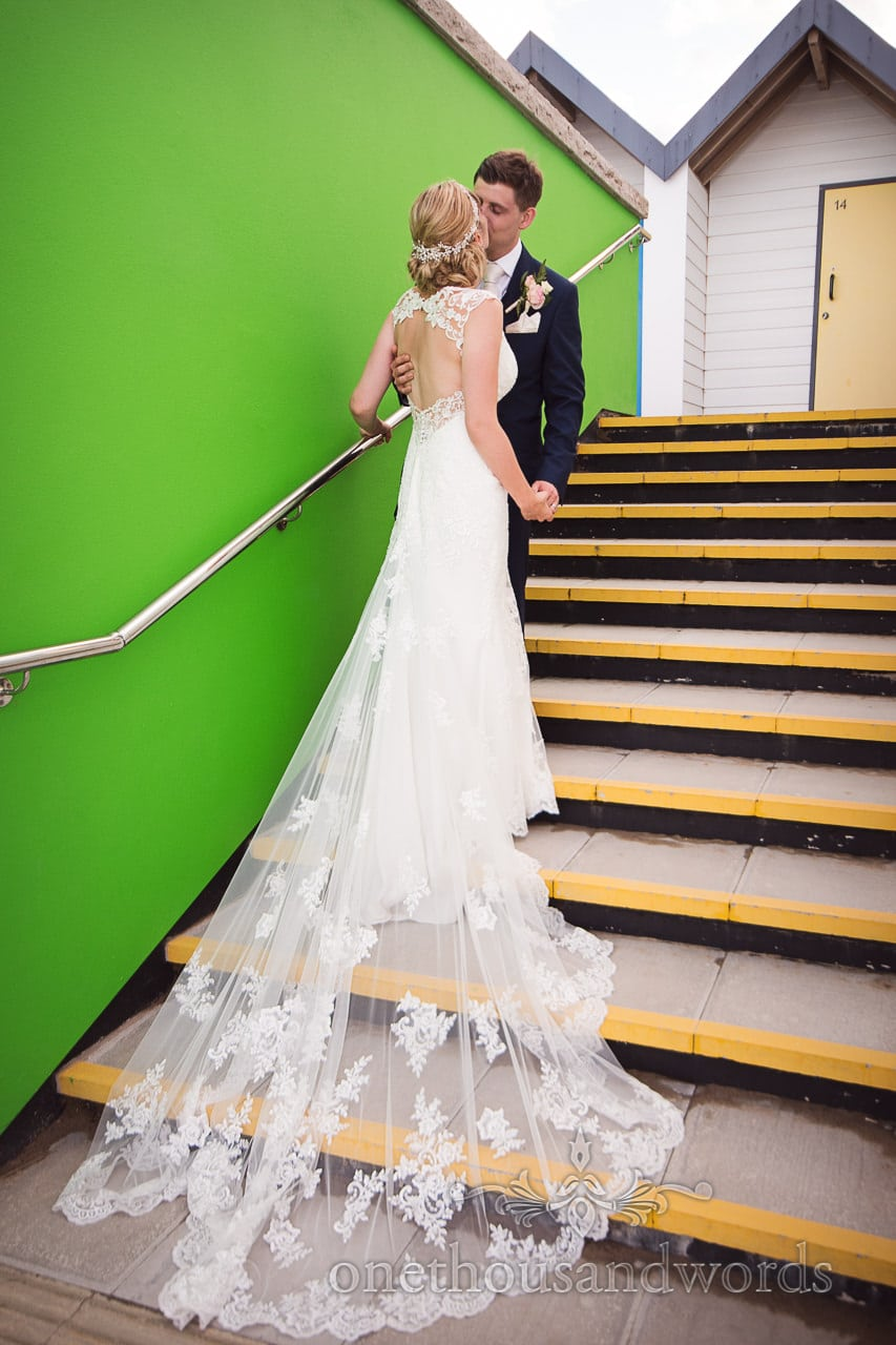 Bride and groom kiss on beach hut staircase by green wall in Swanage, Dorset