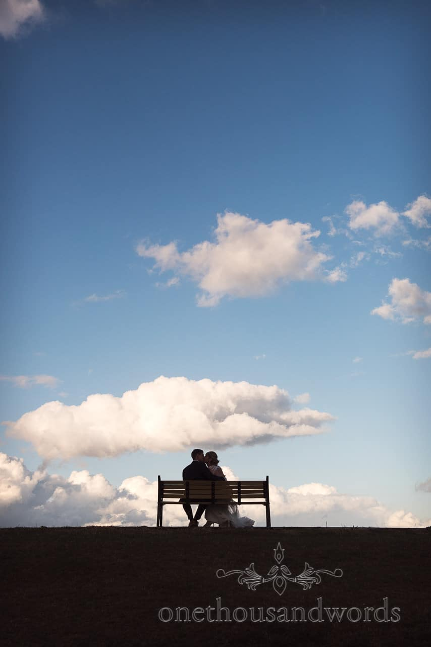 Bride and groom kiss on park bench with blue sky in Swanage park in Dorset