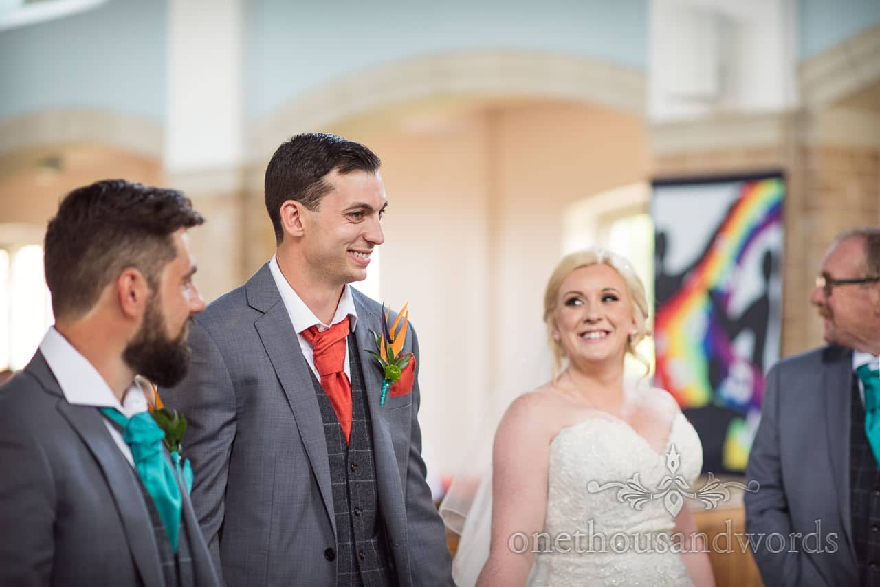 Bride and groom smile during wedding ceremony at St Michael's church in Poole