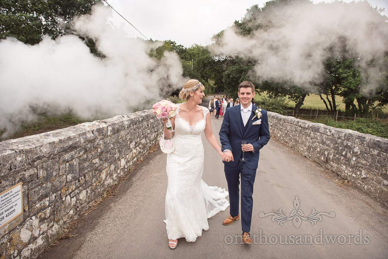 Bride and groom walk above steam train at Harmans Cross Village Hall Wedding