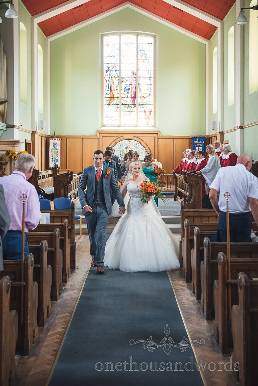 Bride and groom walk down the aisle at St Michael's church wedding in Poole
