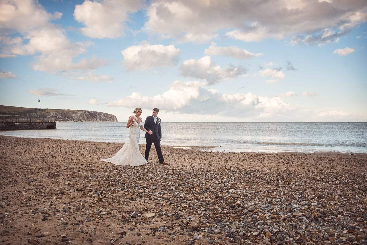 Bride and groom walk hand in hand along Swanage beach on wedding day in Dorset
