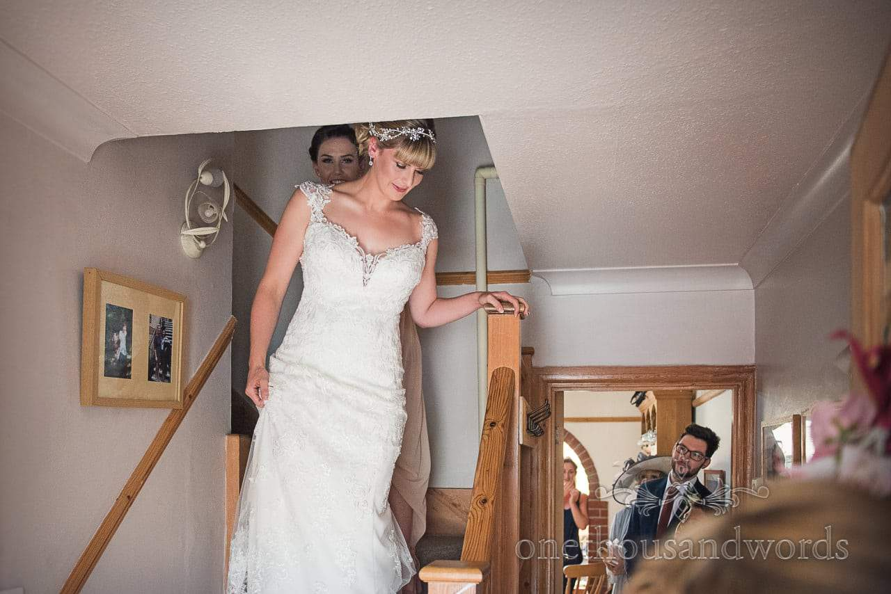 Bride descends stairs revealing her wedding dress on wedding morning in Swanage