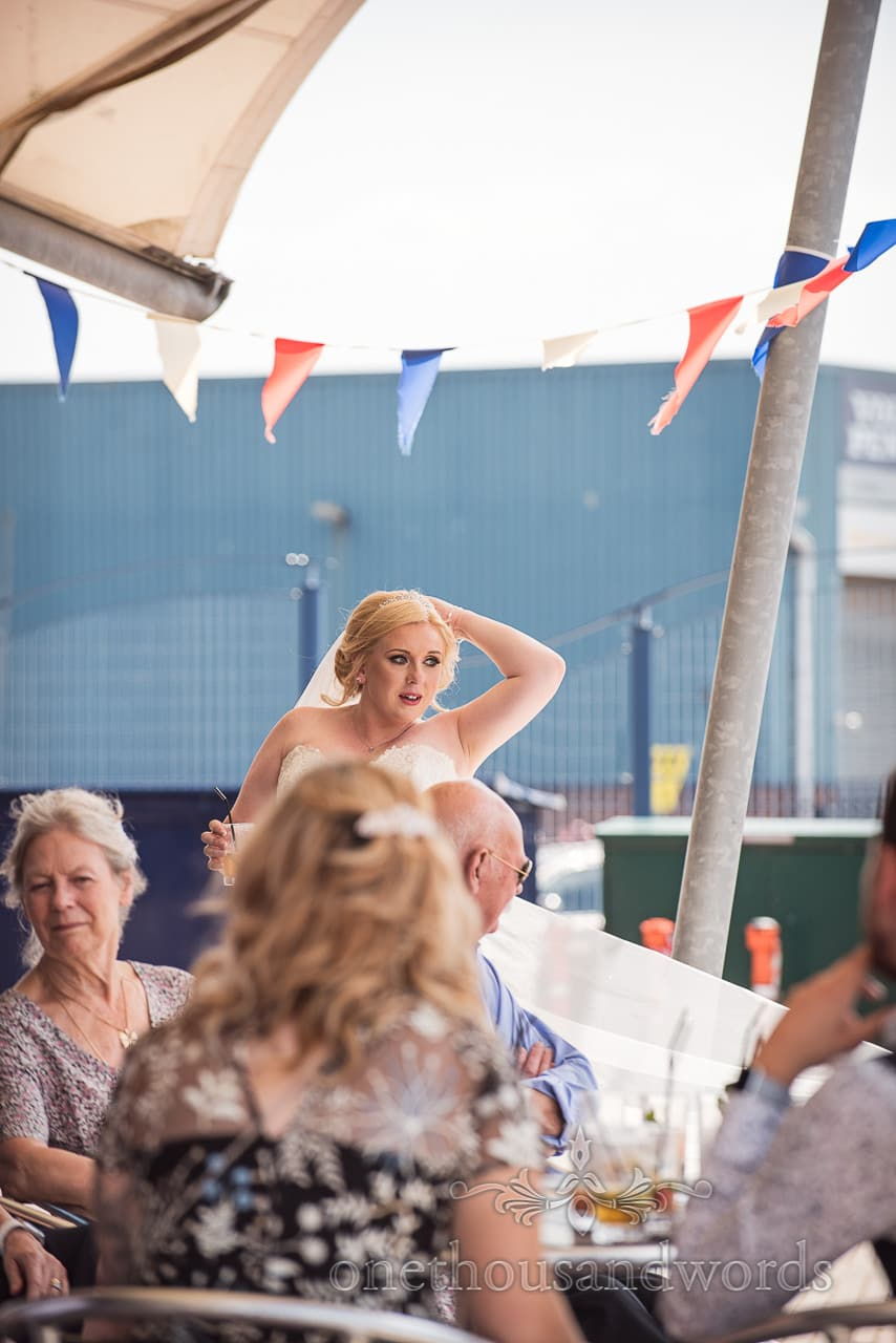 Bride enjoys a drink at RNLI College Wedding drinks reception in Poole, Dorset