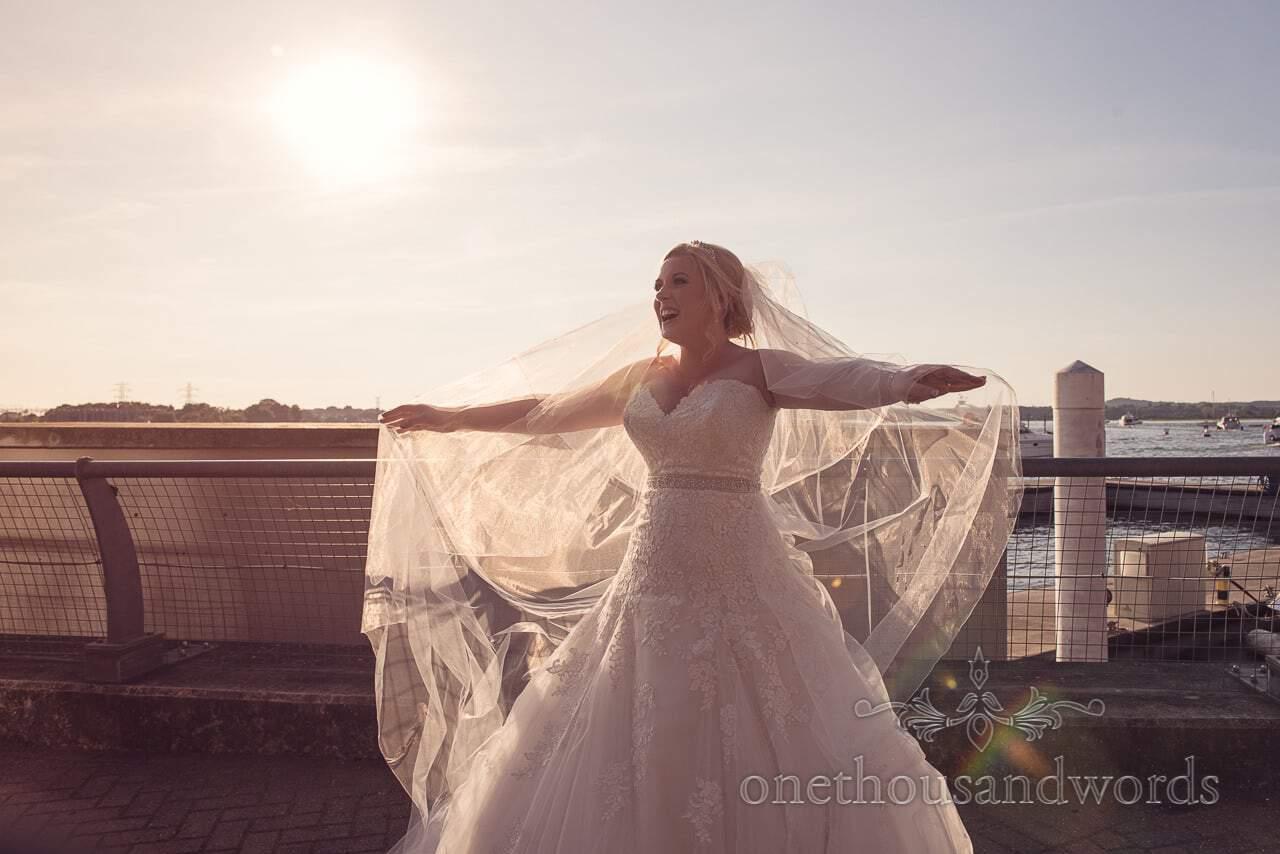 Bride fans out wedding veil in summer sun at RNLI College Wedding
