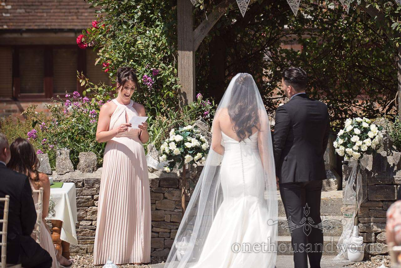 Bride gives reading during outdoor ceremony at Courtyard Wedding