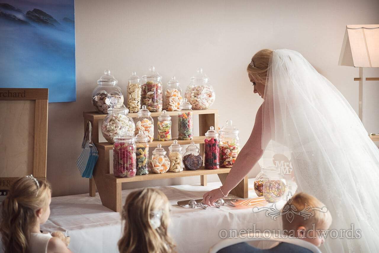 Bride hands out Pick and mix sweets on wooden steps at RNLI College Wedding