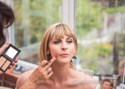 Bride has wedding make up applied during bridal preparation by make-up artist