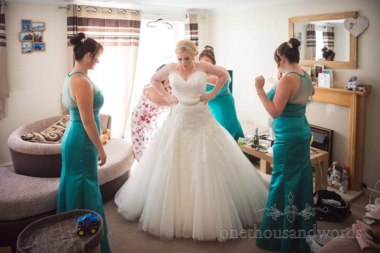 Bride helped into wedding dress with bridesmaids in turquoise on wedding morning