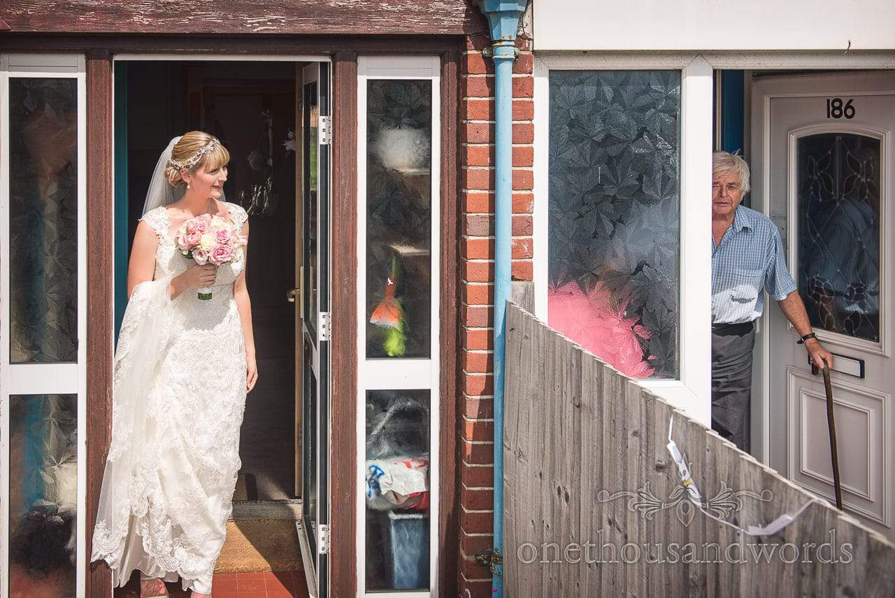 Bride in wedding dress peeks out of family home doorway on wedding morning