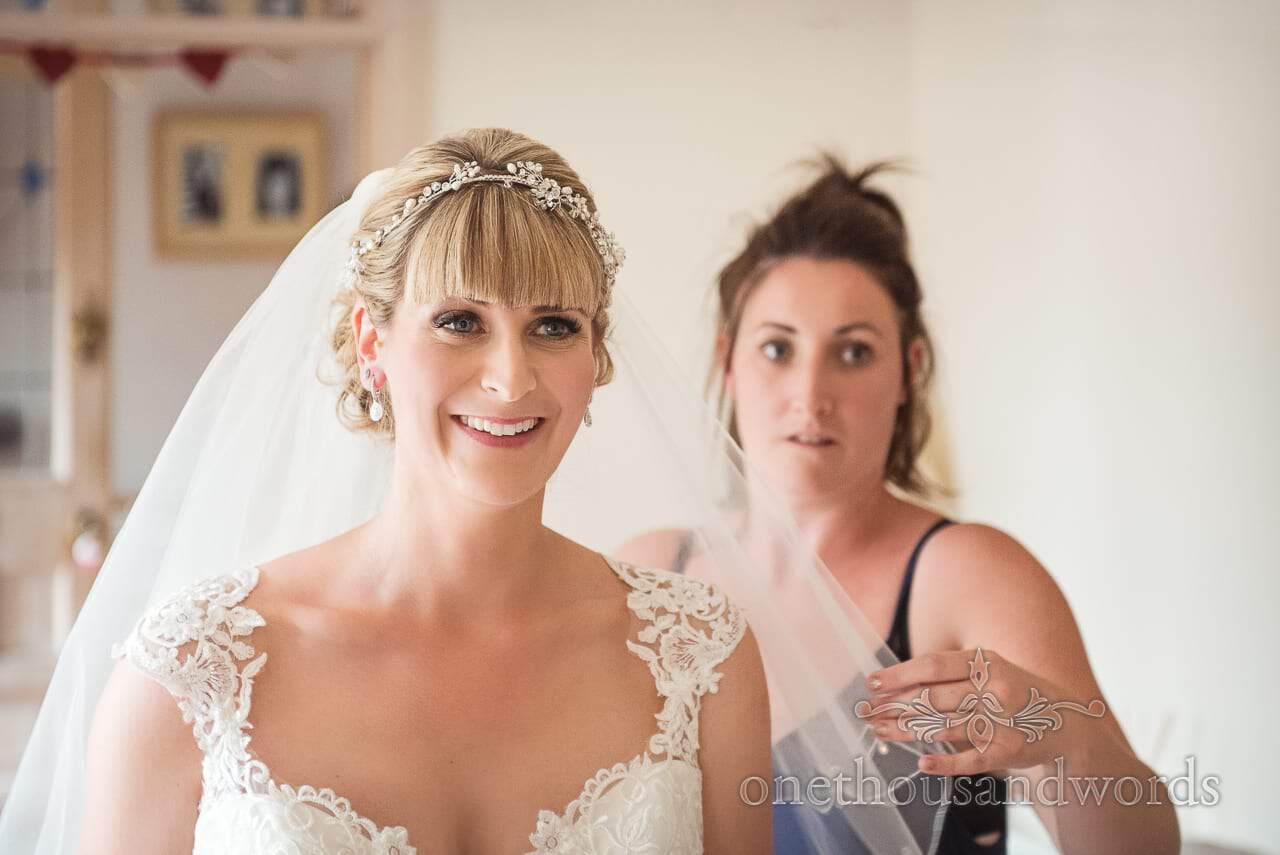 Bride in white detailed wedding dress and veil looks at her reflection in mirror