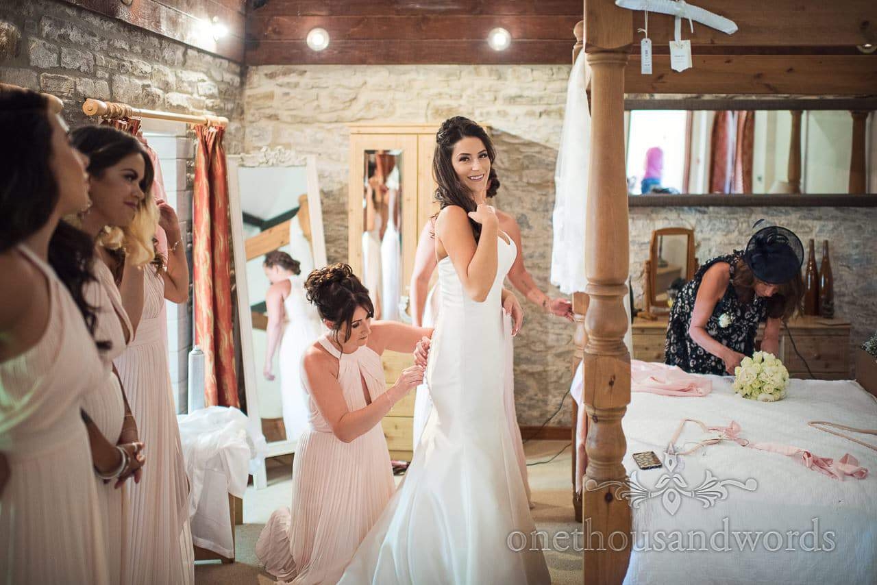 Bride is buttoned into white wedding dress at Kingston Country Courtyard Wedding