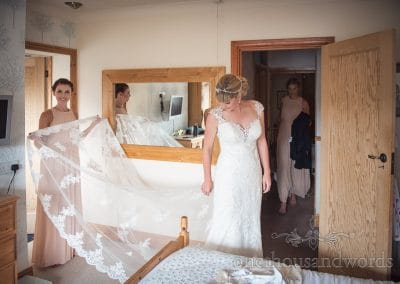 Bride is helped into wedding dress by bridesmaids on wedding morning
