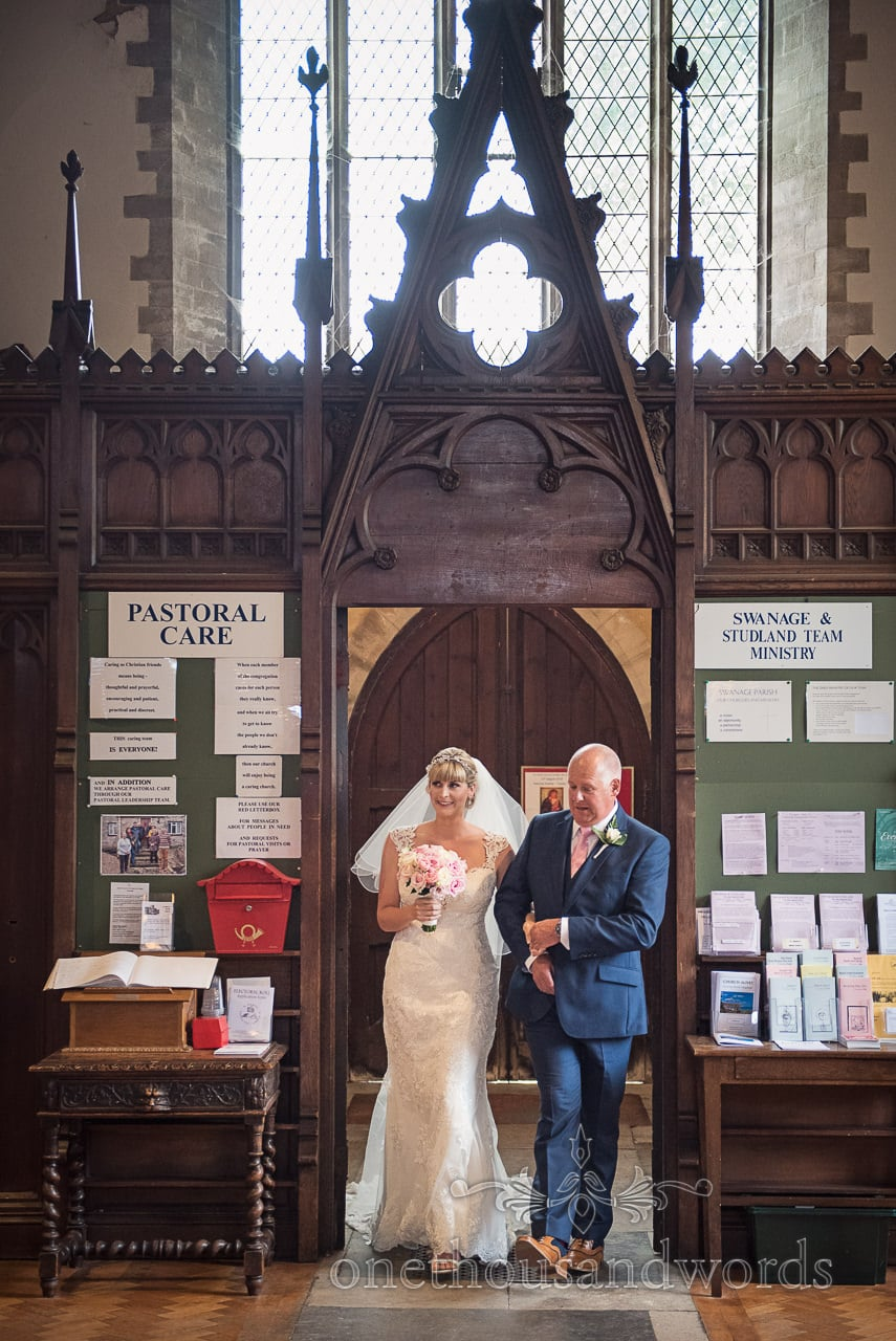 Bride is walked into church wedding ceremony by her father under wooden door