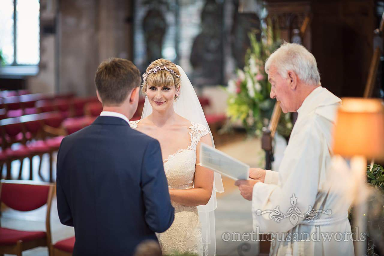 Bride looks into grooms eyes as she makes her wedding vows in church wedding