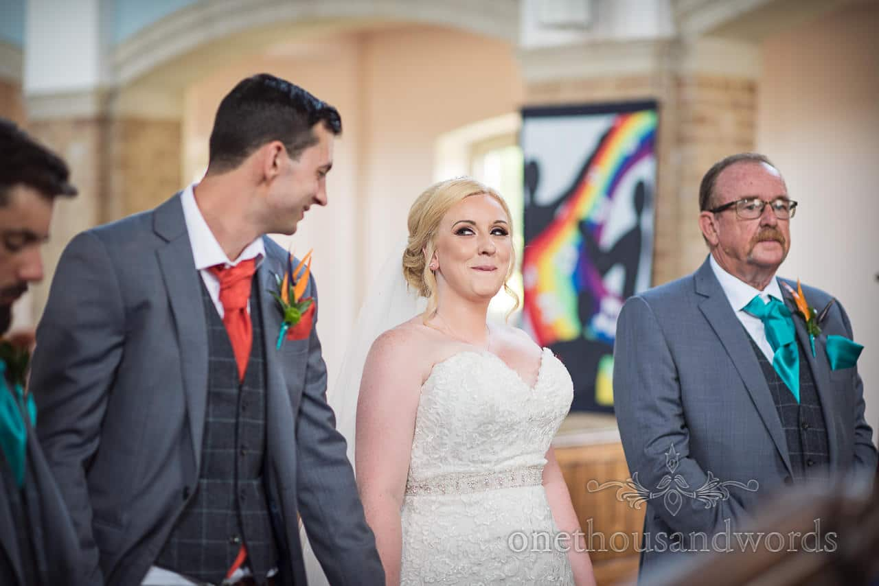 Bride makes cheeky face during wedding ceremony at St Michael's church in Poole