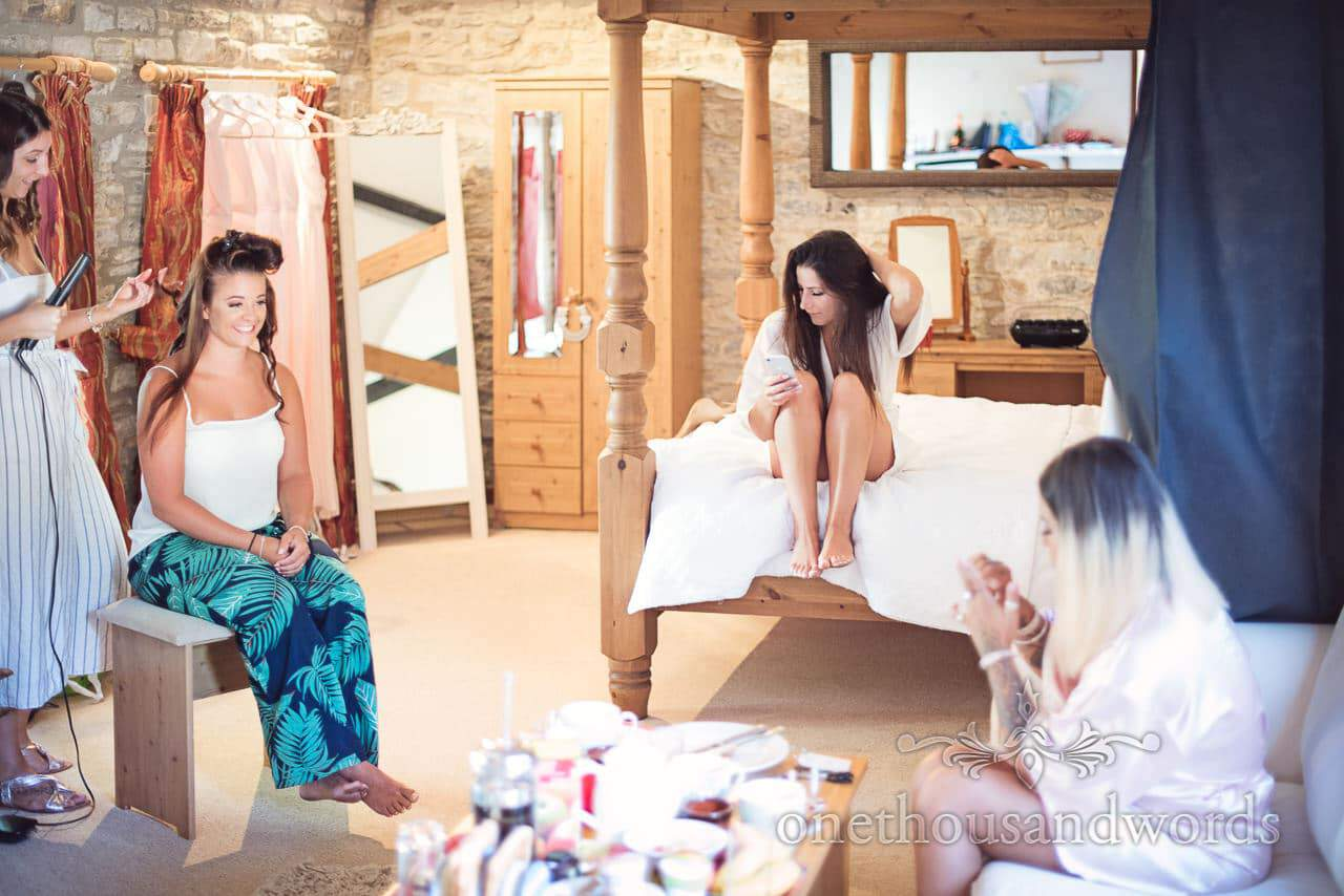 Bride sits on bed among bridesmaid preparation from Country Courtyard Wedding