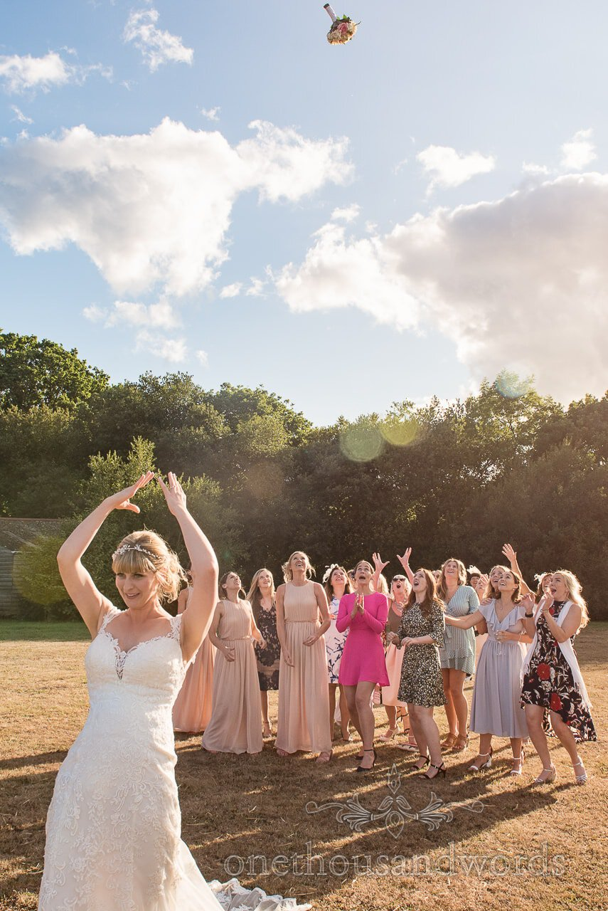 Bride throws bouquet at Harmans Cross Village Hall Wedding Photographs