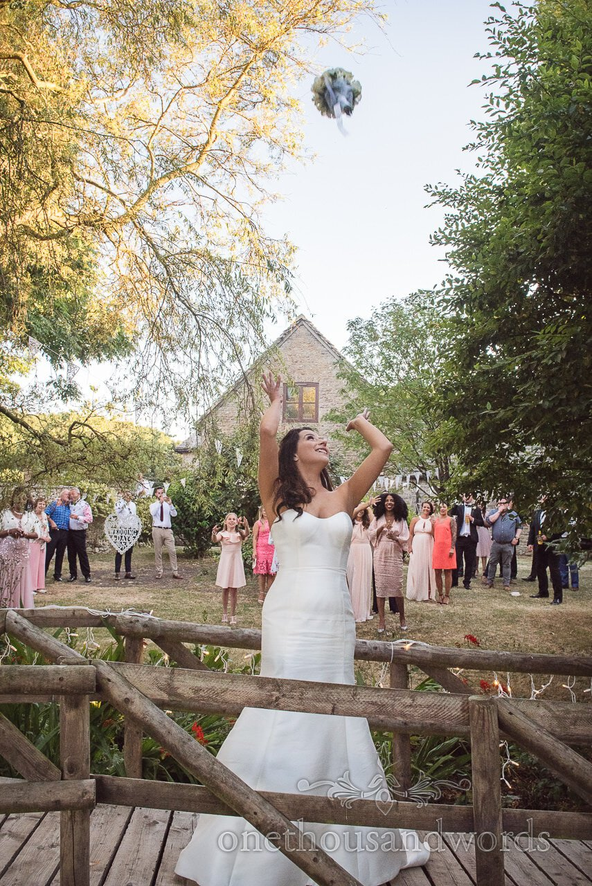 Bride throws her bouquet at Country Courtyard Wedding