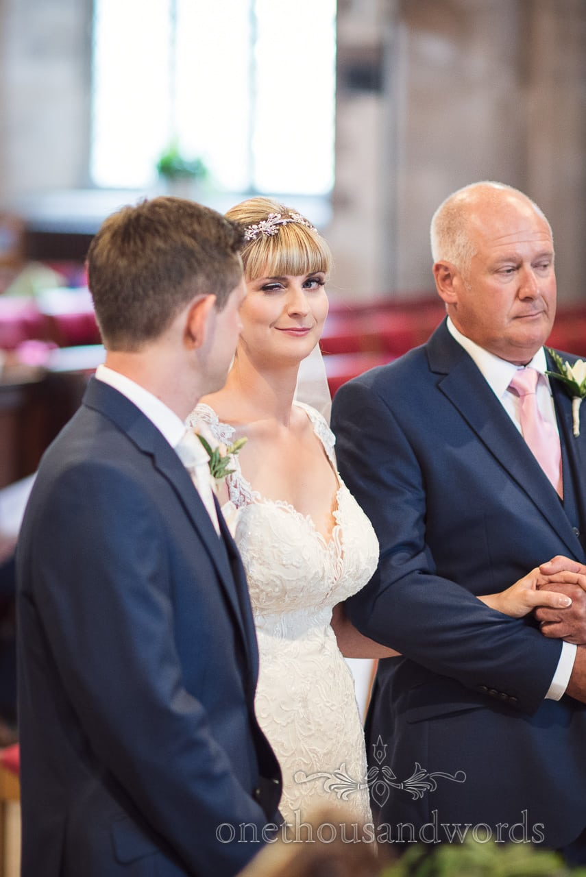 Bride winks at groom when stood at the alter during church wedding ceremony
