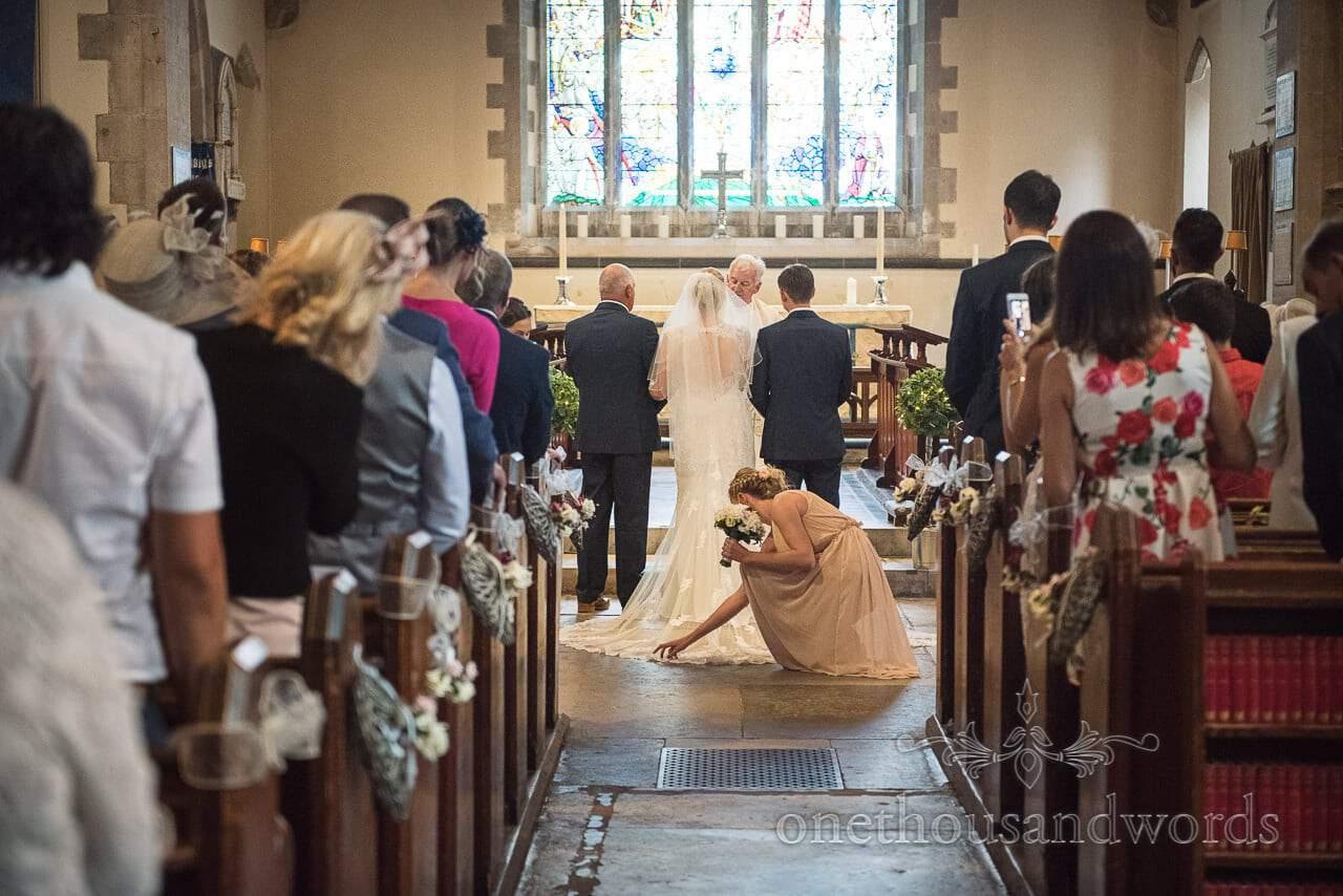 Bridesmaid adjusts brides brides wedding dress during church wedding ceremony