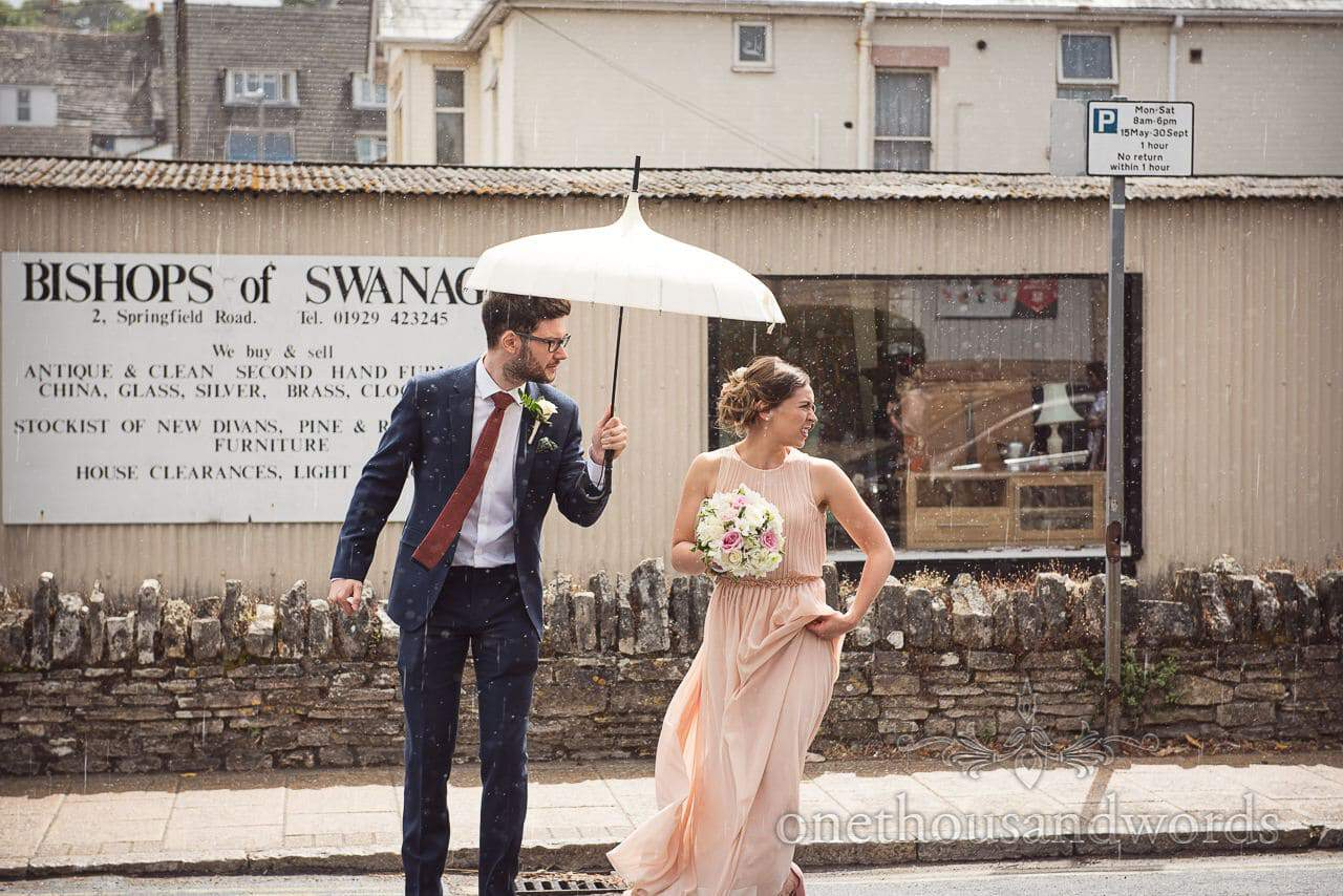 Bridesmaid and grooms man under parasol in rain crossing road in Swanage