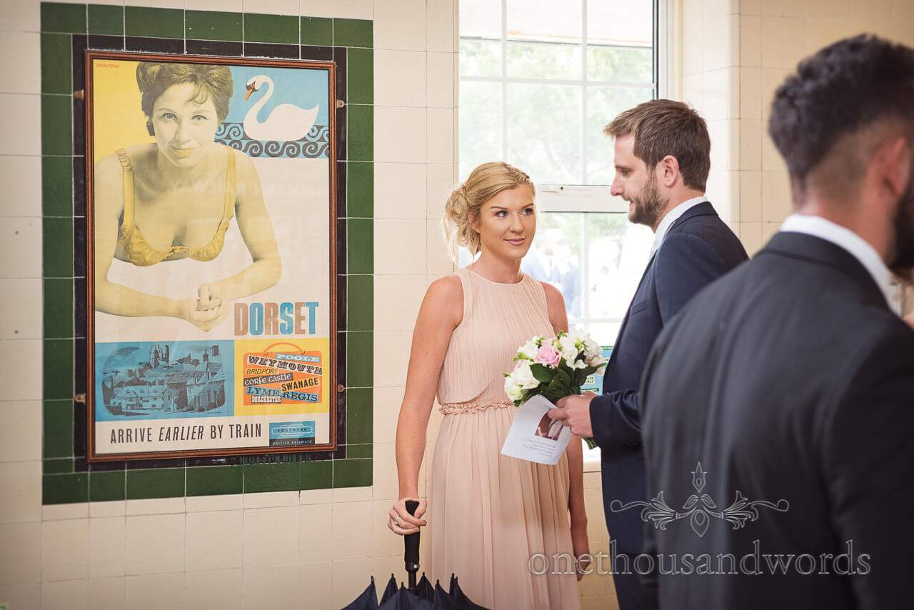 Bridesmaid and groomsmen next to vintage train poster in Swanage railway station