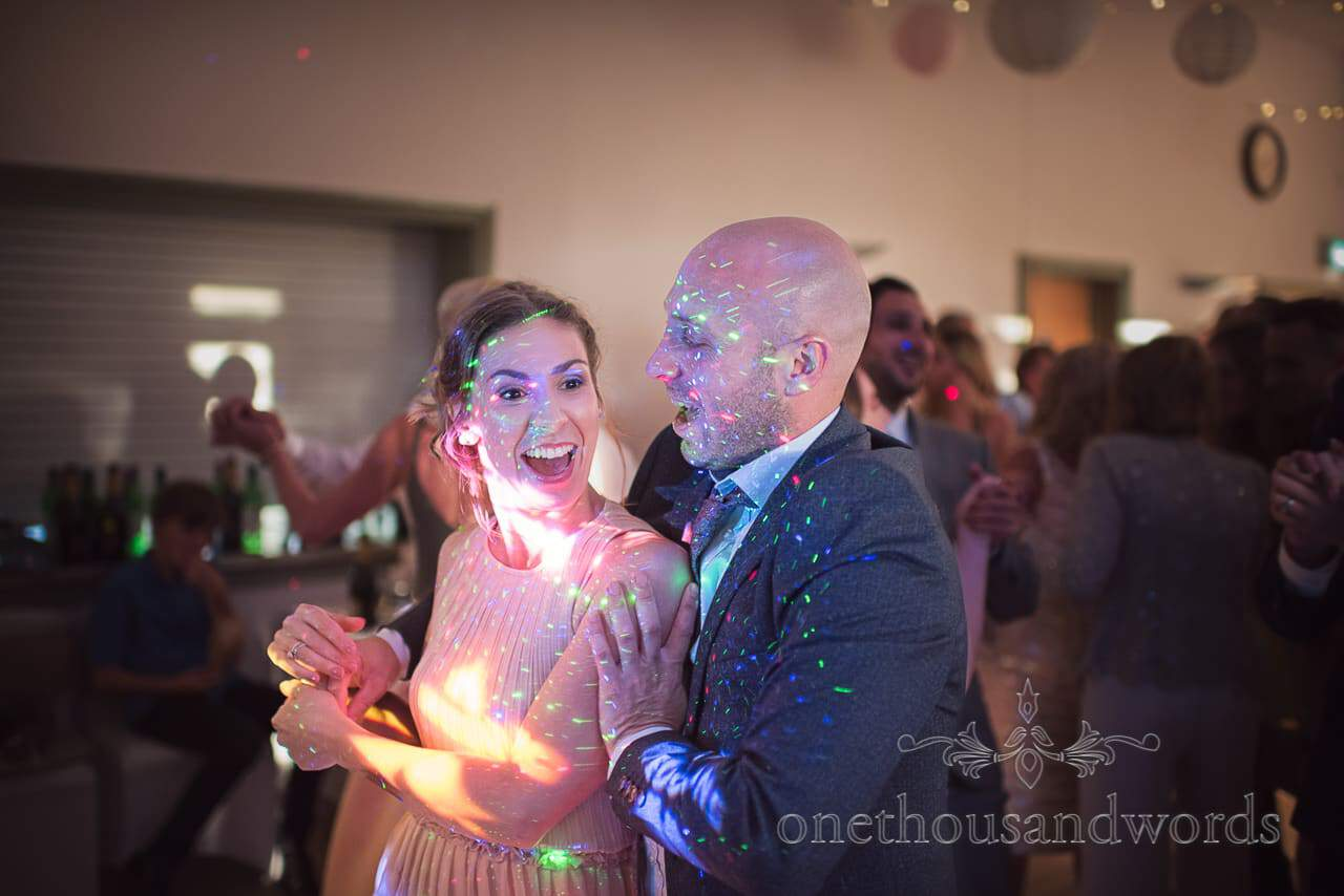Bridesmaid and wedding guest dance on wedding dance floor lit with a million lasers