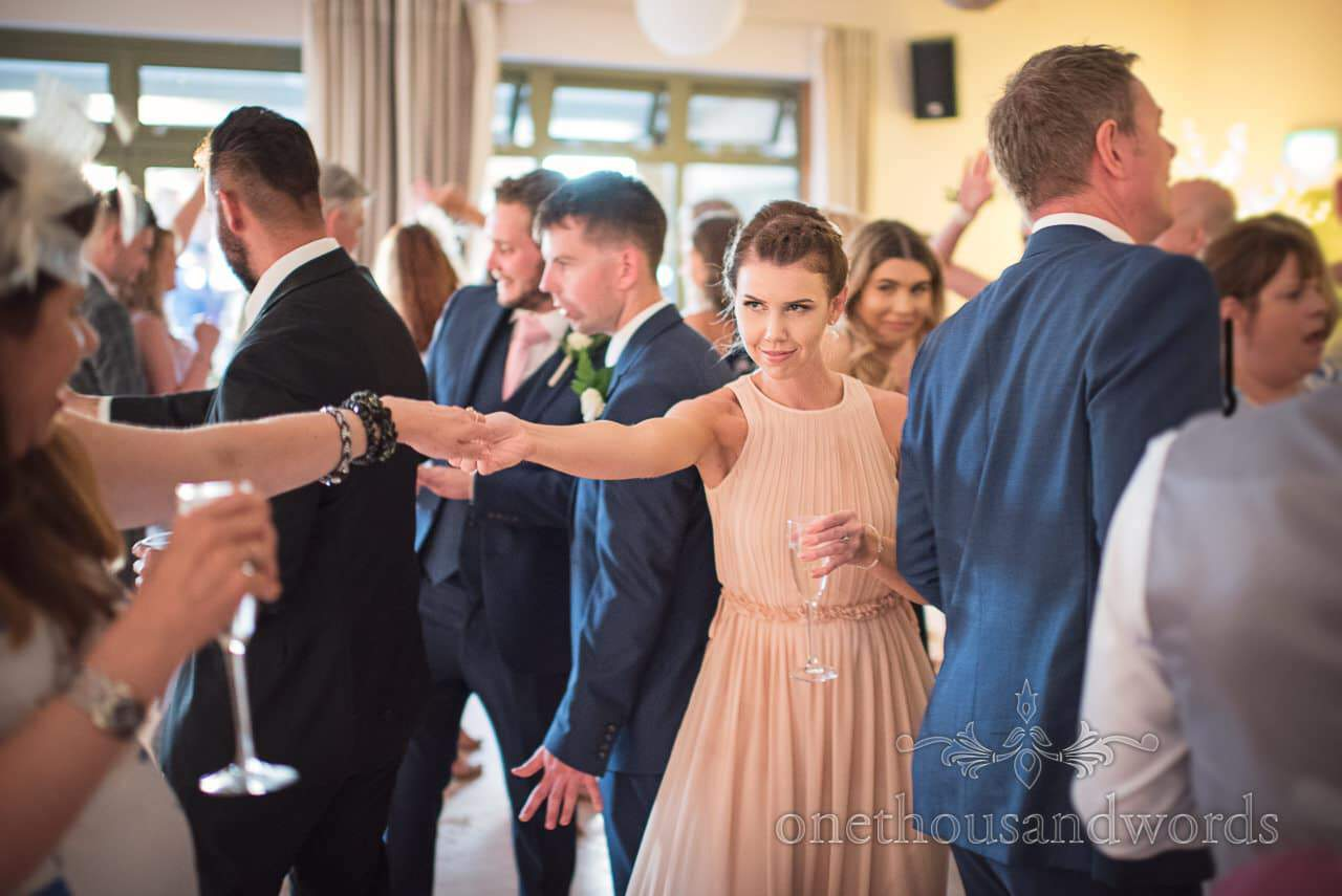 Bridesmaid in pink dances at Harmans Cross Village Hall Wedding Photographs