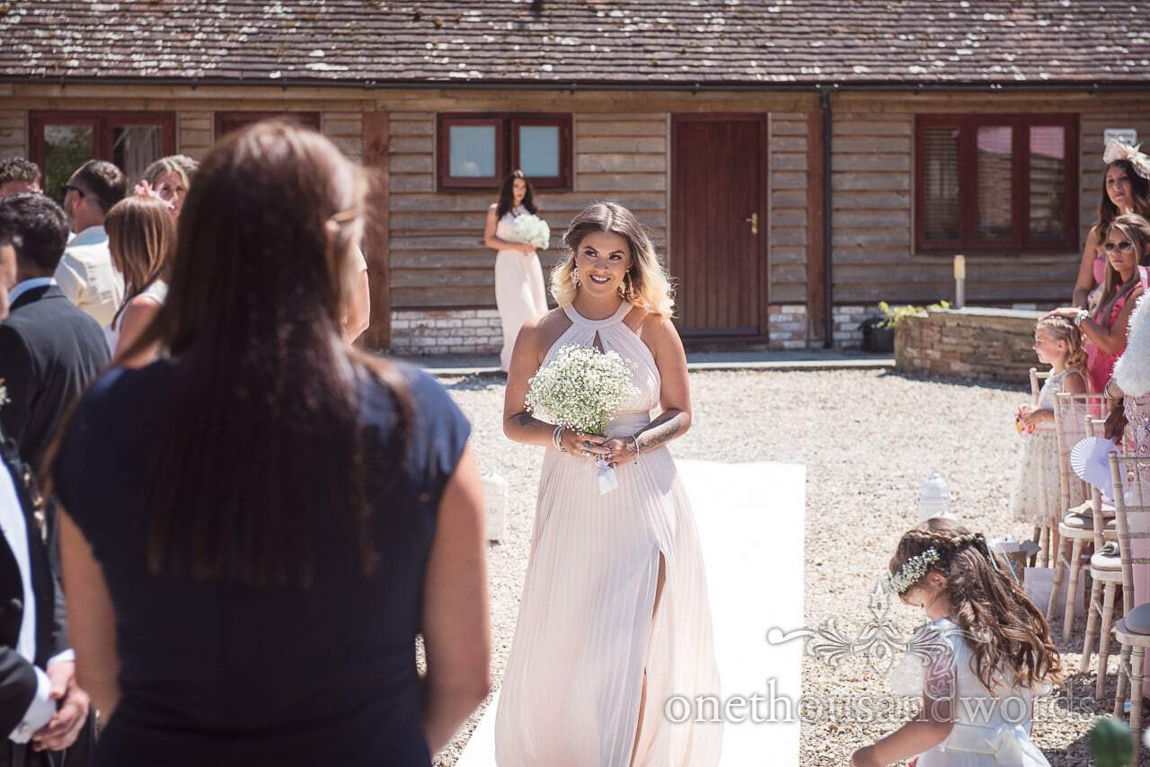 Bridesmaid in pink dress walks down aisle at outdoor Country Courtyard Wedding
