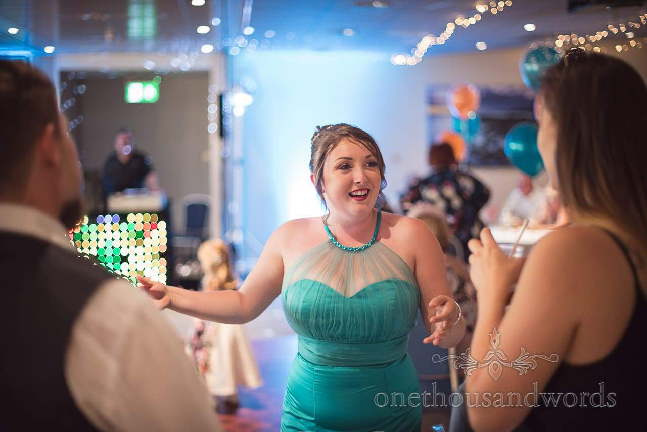 Bridesmaid in turquoise bridesmaids dress dancing at RNLI College Wedding