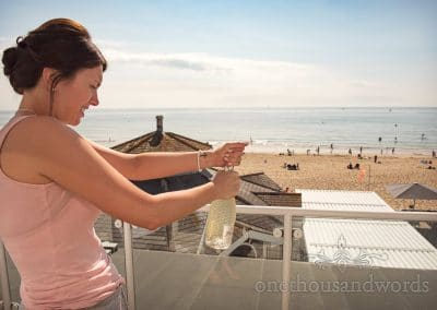Bridesmaid opens wedding Prosecco over beach at Sandbanks Hotel Wedding