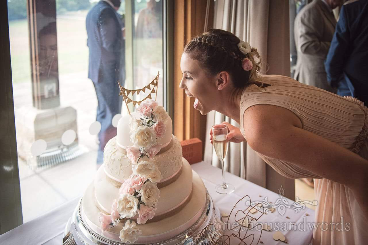 Bridesmaid pretends to take a bit out of wedding cake with icing flowers