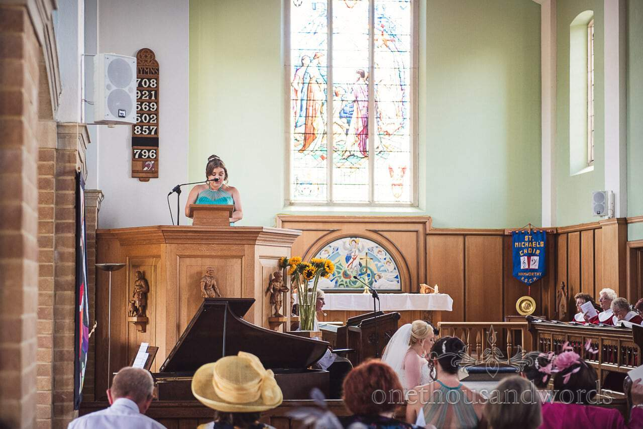 Bridesmaid reading at wedding ceremony at St Michael's church in Poole