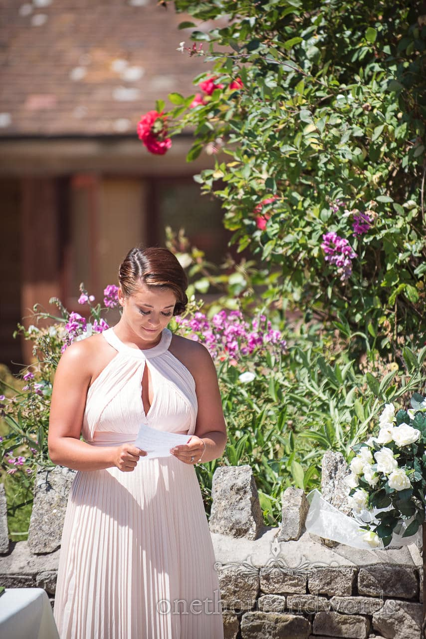 Bridesmaid reading during outdoor ceremony at Country Courtyard Wedding