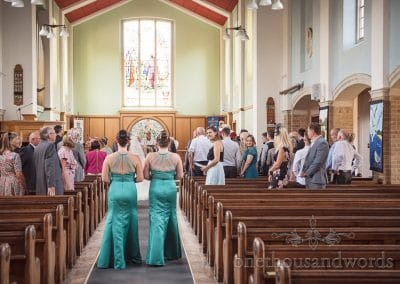 Bridesmaids in turquoise bridesmaids dresses walk up the aisle at Poole church