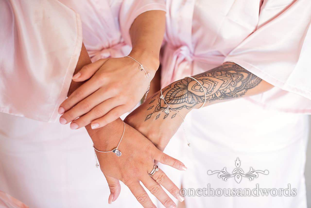 Bridesmaids with tattooed arms show of wedding morning jewellery gifts