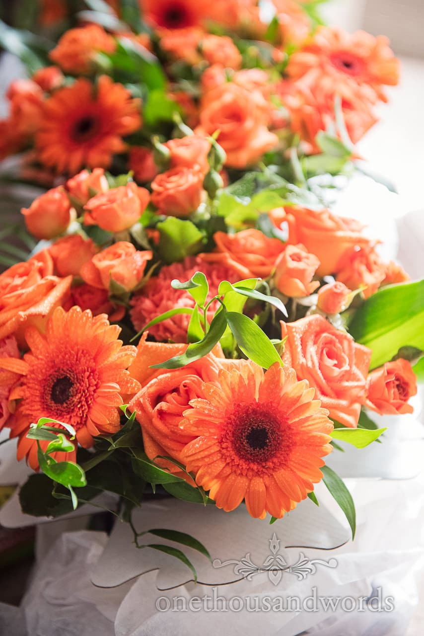 Bright orange and green bouquets from RNLI College Wedding Photographs