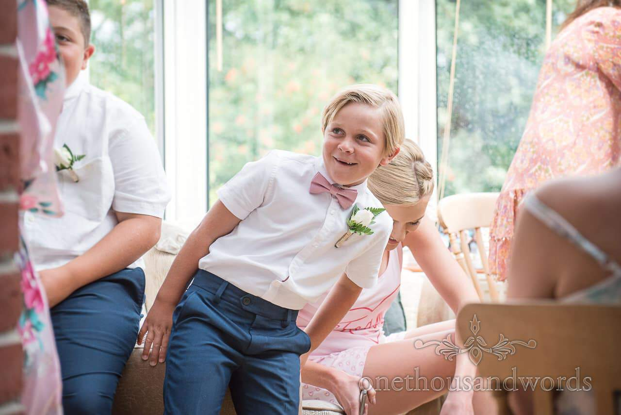 Cheejy page boy with pink bow tie during wedding morning bridal preparations