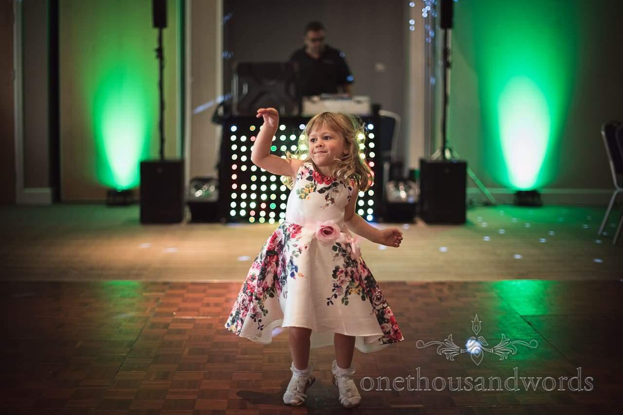 Child weddign dress in floral dress is first onto dance floor at RNLI College wedding