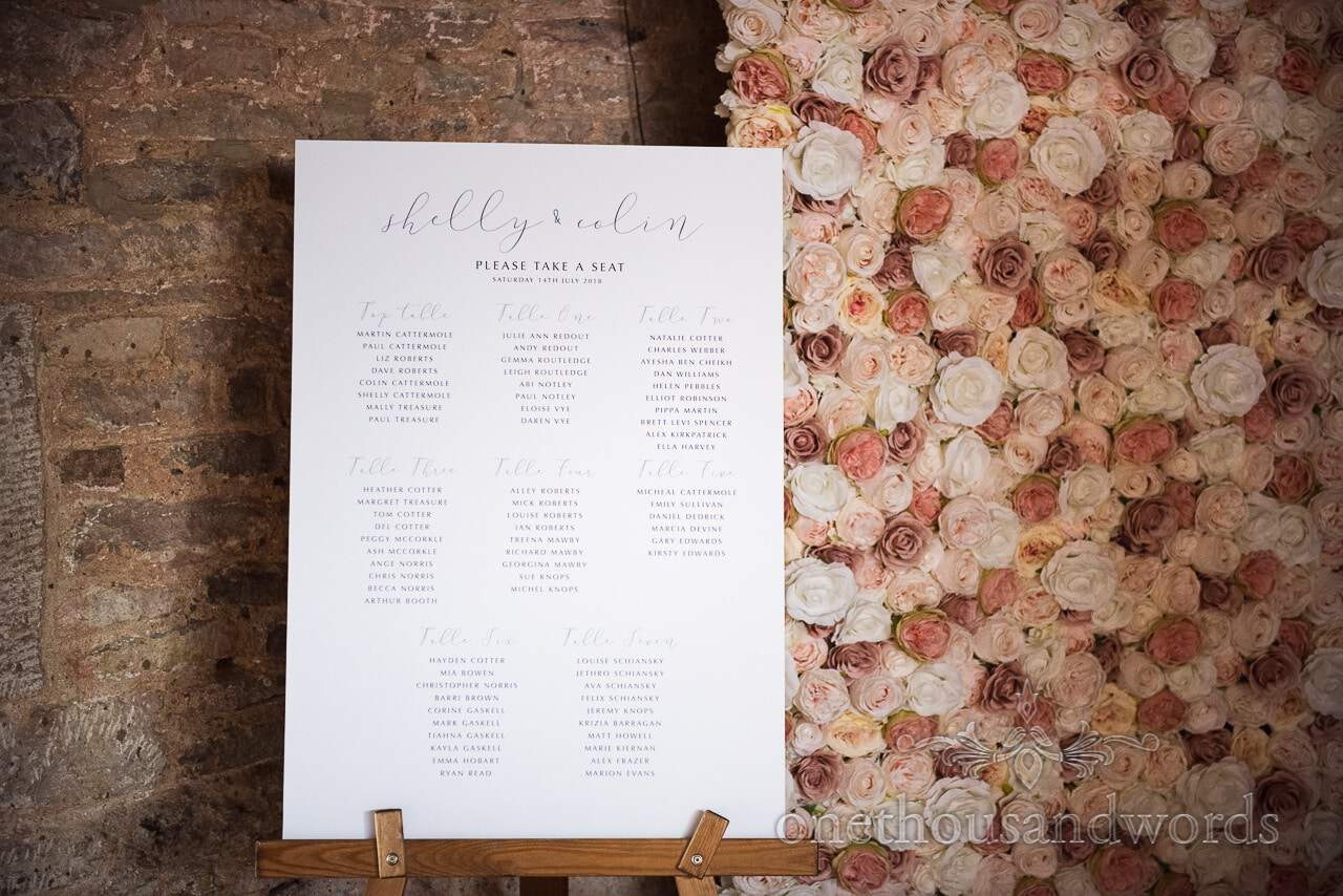 Custom seating plan ans flower wall at Country Courtyard Wedding